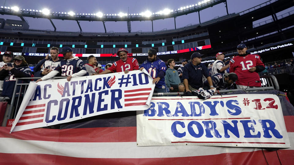 Fans hang signs for New England Patriots quarterback Mac Jones (10) and Tampa Bay Buccaneers quarterback Tom Brady (12) prior to an NFL football game between the New England Patriots and Tampa Bay Buccaneers, Sunday, Oct. 3, 2021, in Foxborough, Mass. (AP Photo/Elise Amendola)