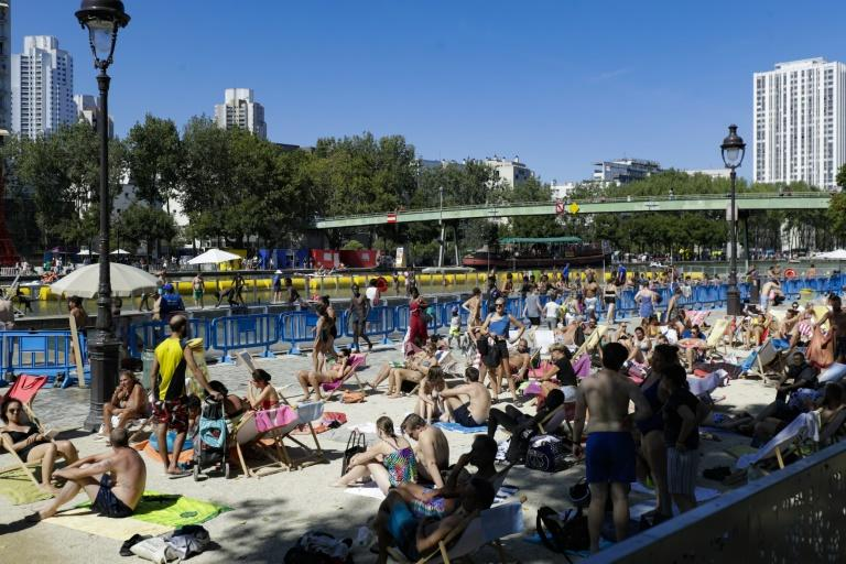 A crowded outdoor swimming pool on a canal in central Paris as people seek relief from near-record temperatures in a heatwave sweeping across Europe
