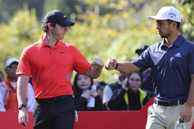 Rory McIlroy of Northern Ireland fist pumps with Xander Schauffele of the United States at right during the HSBC Champions golf tournament held at the Sheshan International Golf Club in Shanghai on Friday, Nov. 1, 2019. (AP Photo/Ng Han Guan)