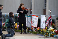 FILE - In this Sunday, Oct. 27, 2019 file photo, Monique Mead plays her violin on the sidewalk outside the Tree of Life synagogue in Pittsburgh on the first anniversary of the shooting at the synagogue, that killed 11 worshippers. (AP Photo/Gene J. Puskar)