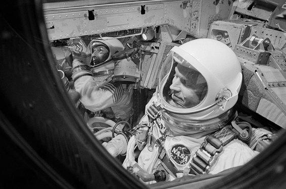 Astronauts Gordon Cooper (foreground) and Charles Conrad are pictured in the Gemini 5 spacecraft moments before the hatches were closed for launch on Aug. 21, 1965.