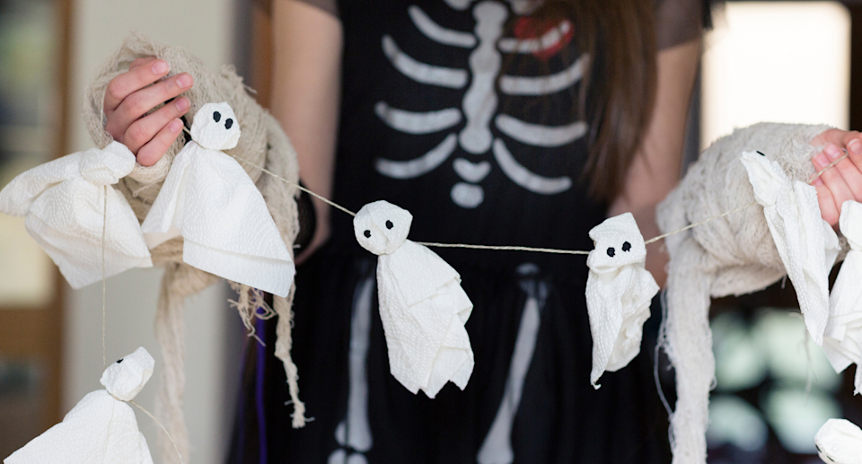 women holding halloween decoration with mini ghosts on a string