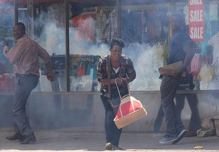 People flee teargas during clashes between police and street vendors in central Harare, Zimbabwe, September 27, 2016. REUTERS/Philimon Bulawayo