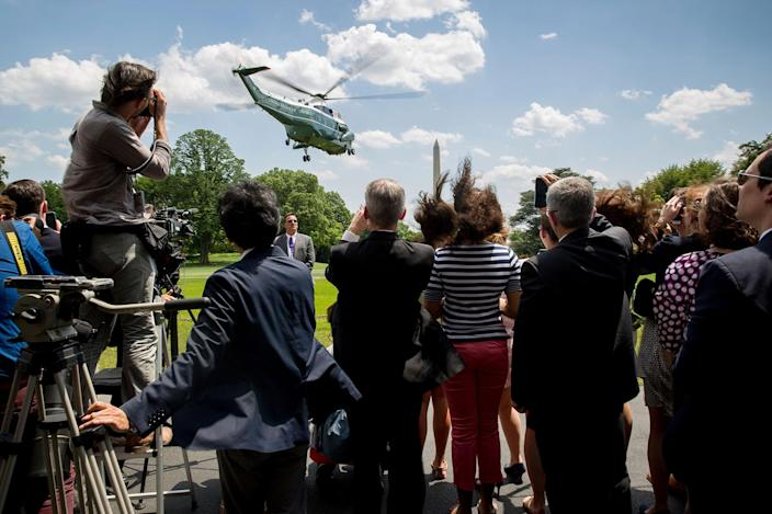 <p>Members of the media and White House staff watch as Marine One, with President Donald Trump aboard, departs from the South Lawn of the White House in Washington, Friday, May 19, 2017, for a short trip to Andrews Air Force Base, Md. (Photo: Andrew Harnik/AP) </p>