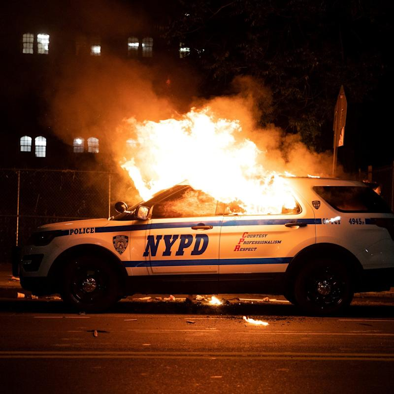 An NYPD police car is set on fire as protesters clash with police during a march against the death in Minneapolis police custody of George Floyd - Reuters