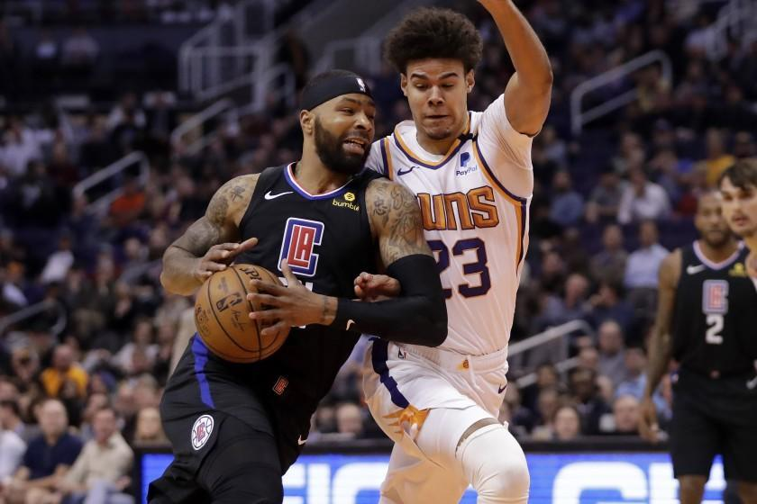 Clippers forward Marcus Morris Sr. drives against Suns forward Cameron Johnson during a game Feb. 26, 2020, in Phoenix.