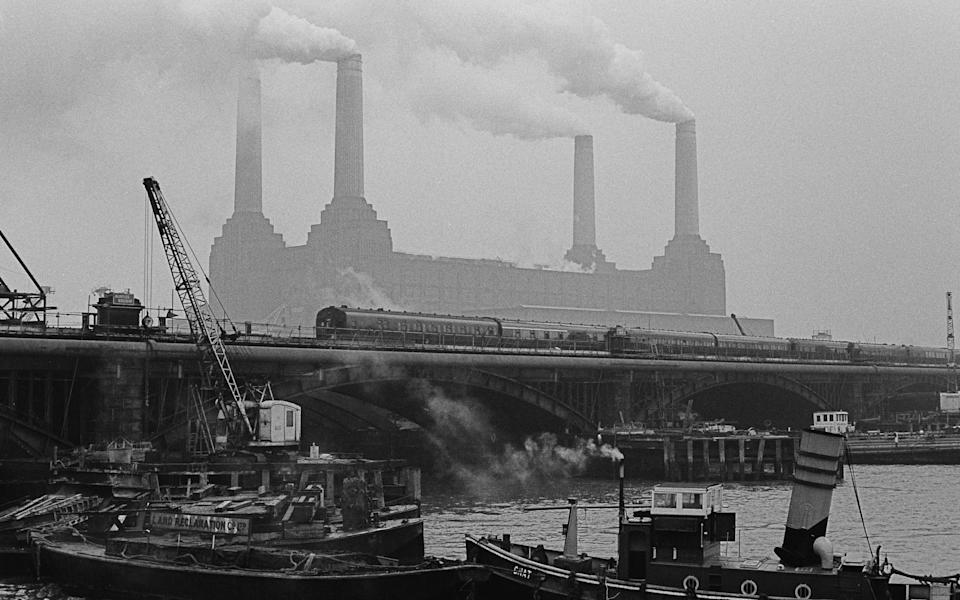 A view across the Thames towards Battersea Power Station, with a train crossing Grosvenor Bridge (aka Victoria Railway Bridge) in the foreground, London, 28th December 1966. (Photo by Chris Morphet/Getty Images)  - Getty