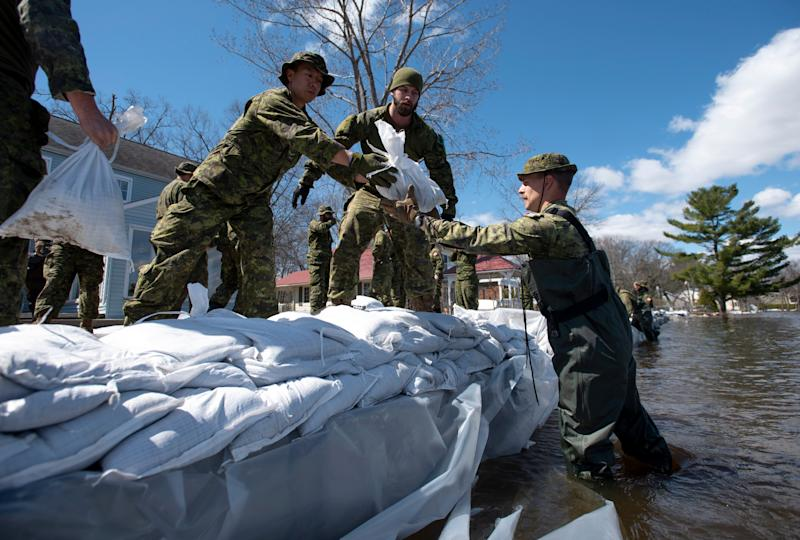 Canadian Forces members build a wall of sandbags to protect a home in the Ottawa community of Constance Bay, on Tuesday, April 30, 2019. For centuries, residents of flood-prone areas have looked to sandbags to stave off rising waters. Flood management experts say that while it's easy to understand why sandbags have become the first line of defence, they may not necessarily be the best one. (Justin Tang/The Canadian Press via AP)