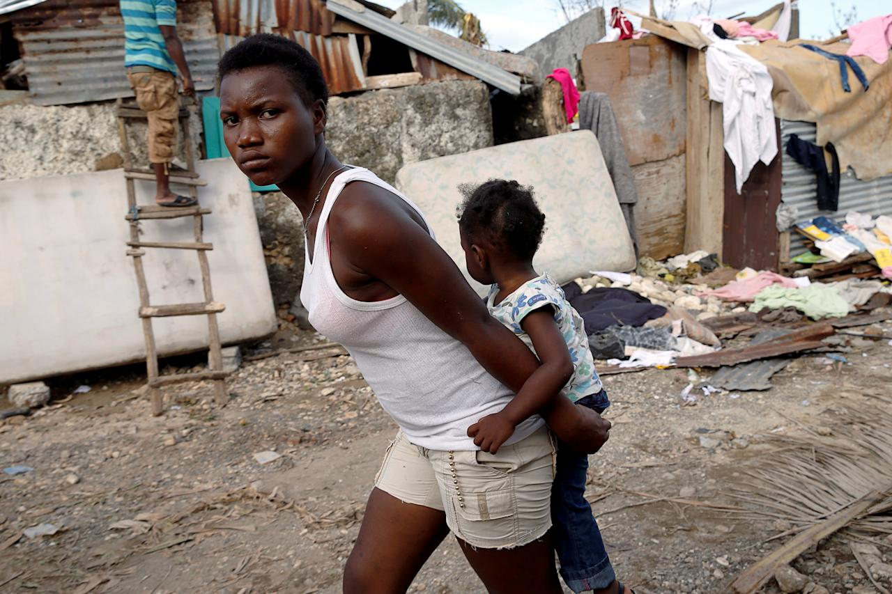 <p>A woman carries a child as they walk in front of destroyed houses after Hurricane Matthew passes Jeremie, Haiti, Oct. 7, 2016. (Photo: Carlos Garcia Rawlins/Reuters) </p>