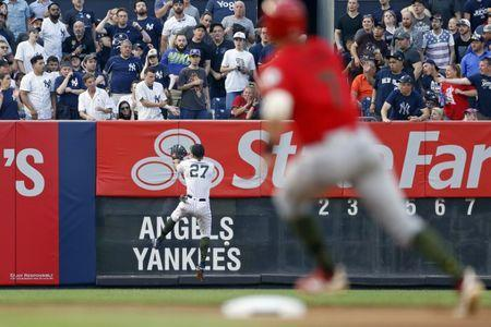 May 26, 2018; Bronx, NY, USA; New York Yankees designated hitter Giancarlo Stanton (27) collides with the wall chasing an RBI double by Los Angeles Angels center fielder Mike Trout as Los Angeles Angels third baseman Zack Cozart (7) rounds second base during the first inning at Yankee Stadium. Mandatory Credit: Adam Hunger-USA TODAY Sports