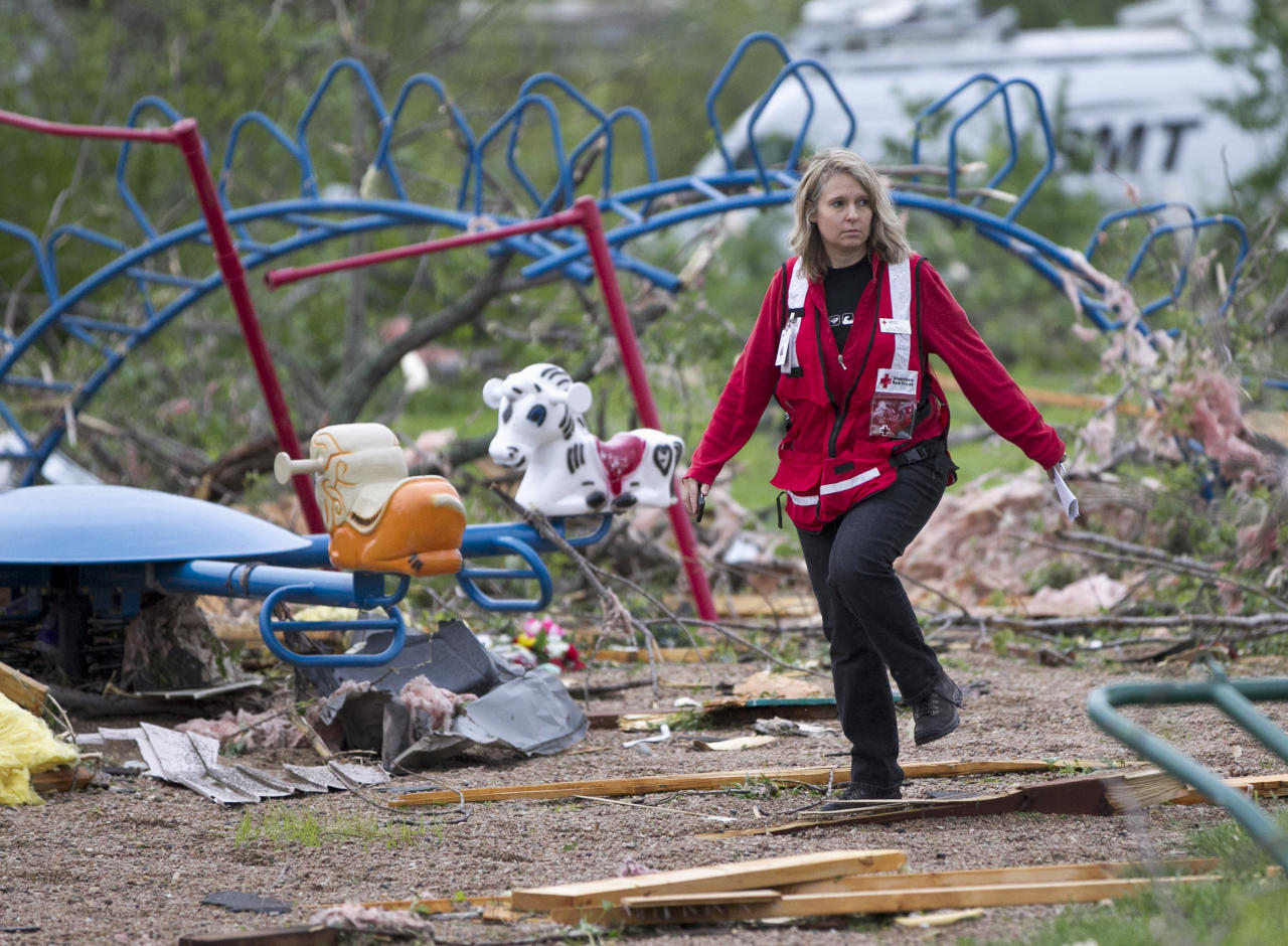 Jill Orton, executive director of the Loess Hills chapter of the Red Cross, walks through a wrecked playground as she surveys damage in Thurman, Iowa, Sunday, April 15, 2012. A large part of the town in the western part of the state was destroyed Saturday night, possibly by a tornado, but no one was injured or killed. Fremont County Emergency Management Director Mike Crecelius said about 75 percent of the 250-person town was destroyed. (AP Photo/Nati Harnik)