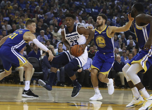 Jimmy Butler (23) drives between Warriors Jonas Jerebko, left, and Klay Thompson (11) during the first half Friday night. (AP)