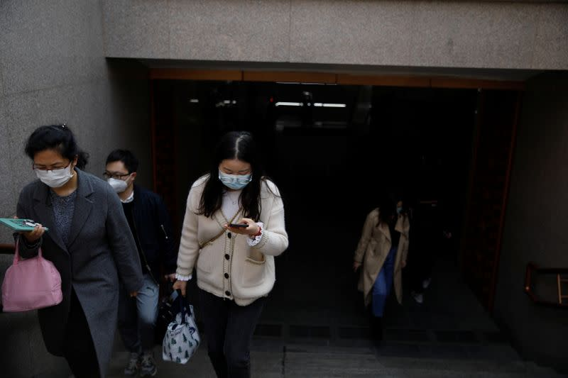 People wearing face masks exit a subway station following an outbreak of the coronavirus disease (COVID-19), in Beijing