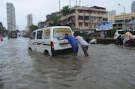 People help a stranded taxi on a flooded road during in Mumbai. (Photo by Arun Patil)