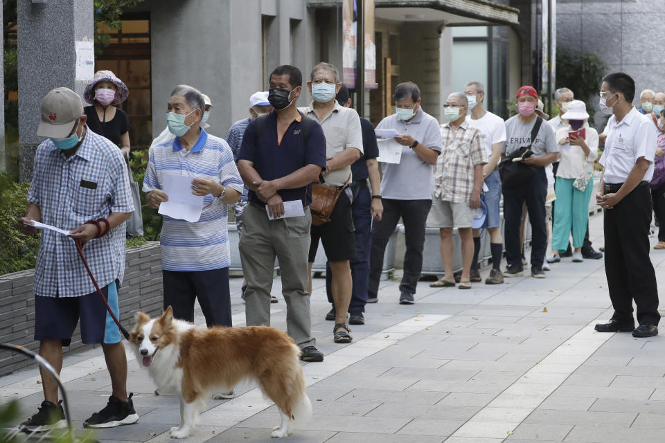 Members of Nationalist Party, or KMT, line up to cast their ballot for election of their party chairman at a polling station in Taipei, Taiwan, Saturday, Sept. 25, 2021. Fraught relations with neighboring China are dominating Saturday's election for the leader of Taiwan's main opposition Nationalist Party. (AP Photo/Chiang Ying-ying)