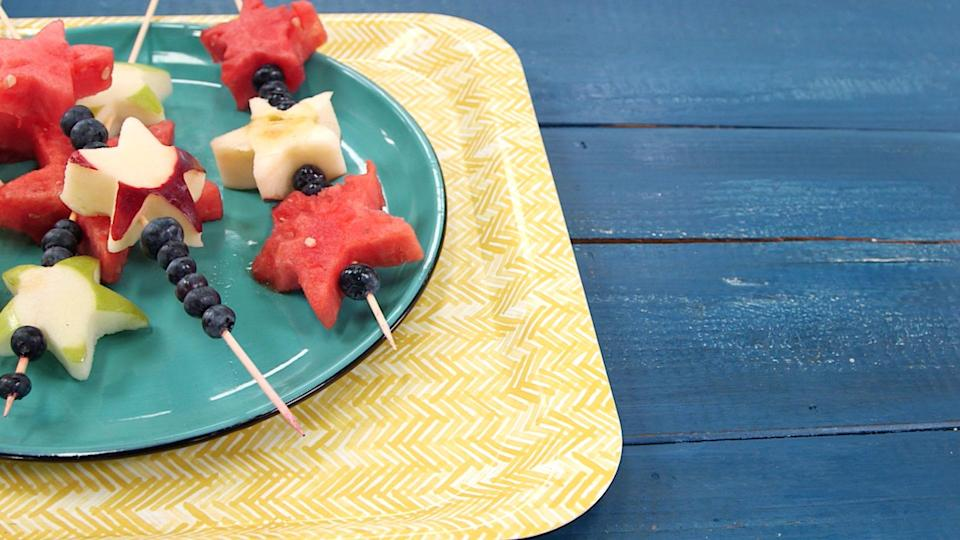 """<p><strong>Recipe:</strong> <a href=""""https://www.southernliving.com/recipes/summer-fruit-skewers"""" rel=""""nofollow noopener"""" target=""""_blank"""" data-ylk=""""slk:Summer Fruit Skewers"""" class=""""link rapid-noclick-resp"""">Summer Fruit Skewers</a></p> <p>Festive and fun, these fruit skewers are a sweet side dish. Enlist the help of little ones for cutting and skewering the fruit as a fun project before guests come over.</p>"""