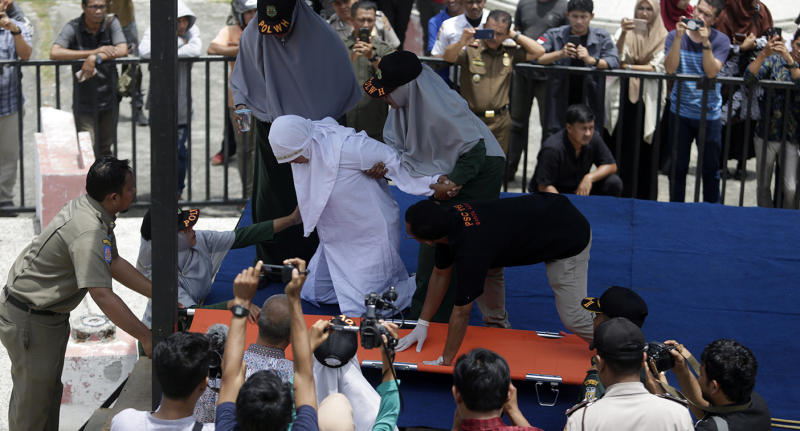 A woman collapsed after being whipped in public in Banda Aceh, Indonesia