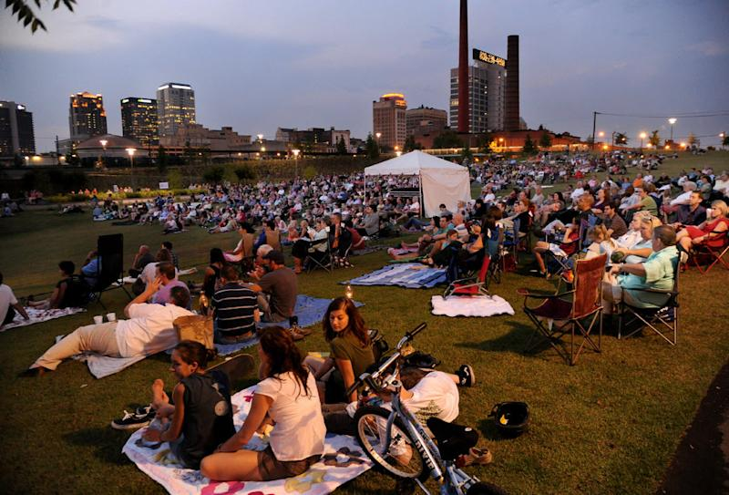 In a June 10, 2011 photo, people sit on a hillside during a performance by the Alabama Symphony Orchestra in Railroad Park in Birmingham, Ala. Long haunted by black-and-white newsreel footage of the fire hoses and police dogs city leaders turned on blacks demonstrating for civil rights, the city has a new vibe that's generating buzz all its own 50 years later. The urban park is built on what was an unsightly lot strewn with weeds and gravel along railroad lines. (The Birmingham News/Mark Almond) MAGS OUT