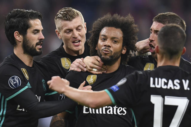 Madrid's Marcelo, center, is congratulated by his teammates after scoring his side's first goal during the soccer Champions League first leg semifinal soccer match between FC Bayern Munich and Real Madrid in Munich, southern Germany, Wednesday, April 25, 2018. (Sven Hoppe/dpa via AP)