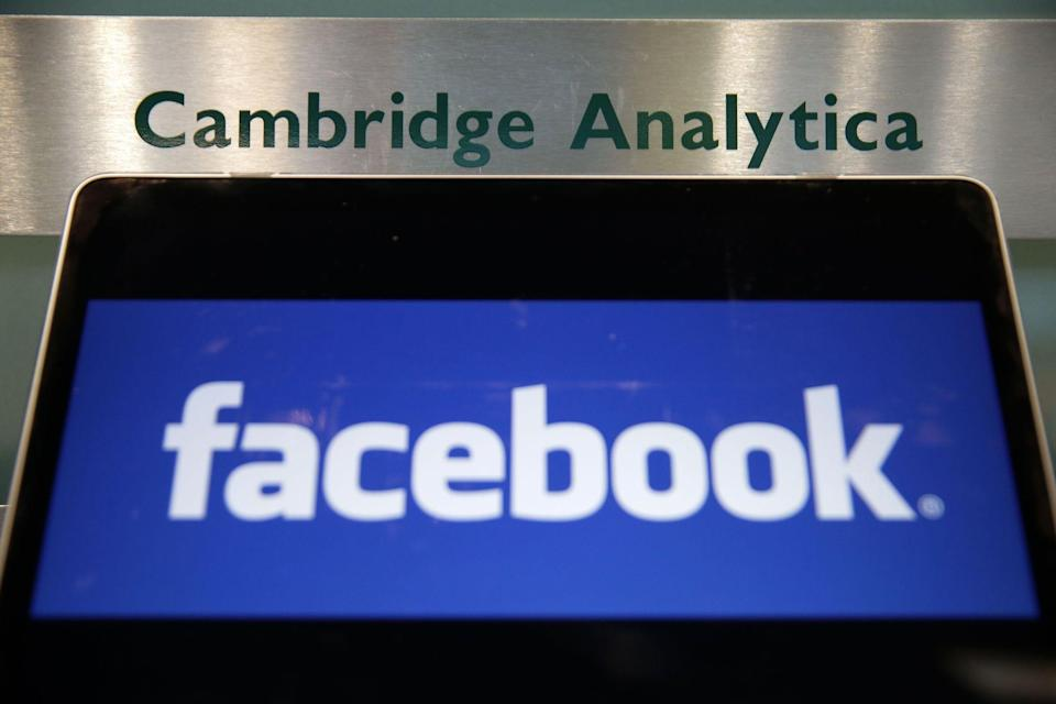 Catastrophe: A laptop showing the Facebook logo is held alongside a Cambridge Analytica sign at the entrance to the building housing the offices of Cambridge Analytica, in central London on March 21, 2018. Photo: DANIEL LEAL-OLIVAS/AFP/Getty Images