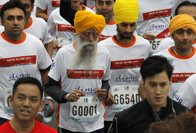 Centenarian marathon runner Fauja Singh, 101, center, originally from Beas Pind, in Jalandhar, India but who now lives in London, runs in a 10-kilometer race, held as part of the annual Hong Kong Marathon, in Hong Kong Sunday, Feb. 24, 2013. Singh will retire from public racing after competing in the marathon. (AP Photo/Vincent Yu)