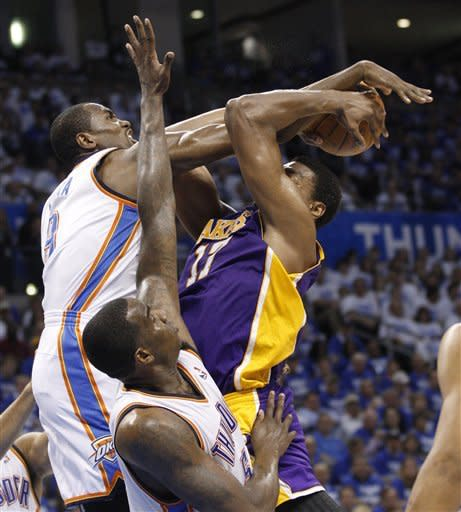 Oklahoma City Thunder forward Serge Ibaka, left, blocks a shot by Los Angeles Lakers center Andrew Bynum during the second quarter in Game 2 of an NBA basketball playoffs Western Conference semifinal, in Oklahoma City on Wednesday, May 16, 2012. (AP Photo/Sue Ogrocki)