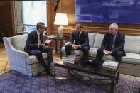 Greece's Prime Minister Kyriakos Mitsotakis, left, talks with UEFA President Aleskander Ceferin, centre, and FIFA Vice-President Greg Clarke, during their meeting in Athens, Tuesday, Feb. 25, 2020. Mitsotakis requested UEFA's help to clean up Greek soccer last month and has said he was willing to request expulsion of Greece's teams from European competition and even suspend the league unless major clubs sign up to a reform plan aimed stamping out match-related violence and widespread allegations of corruption in the sport. (AP Photo/Petros Giannakouris)