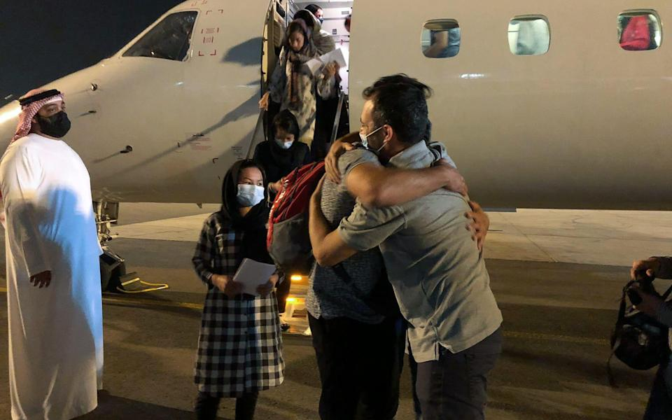 Yotam Polizer, CEO of IsraAid, right, embraces the Afghan evacuees as they arrive in the United Arab Emirates - IsraAid/IsraAid