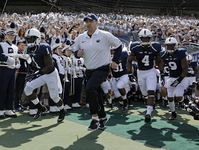 In this Sept. 7, 2013, photo, Penn State coach Bill O' Brien leads his team onto the field at Beaver Stadium for an NCAA college football game against Eastern Michigan in State College, Pa. Two people familiar with the negotiations say O'Brien has reached an agreement to coach the Houston Texans. The people spoke to The Associated Press on the condition of anonymity because an official announcement hasn't been made. (AP Photo/Gene J. Puskar)