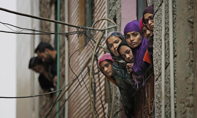 Indian Muslim women look out of a window as security officers patrol a street in Delhi