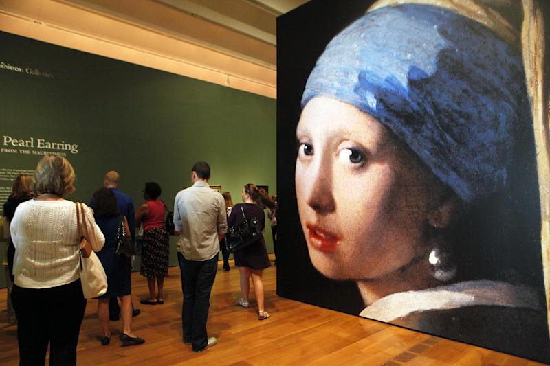 """This June 19, 2013 photo shows visitors entering the """"Girl with a Pearl Earring: Dutch Paintings from the Mauritshuis"""" exhibit during a media preview at the High Museum of Art in Atlanta. The exhibit, which opens Sunday and runs through Sept. 29, includes Johannes Vermeer's famous """"Girl With a Pearl Earring"""" painting and 34 other works from the Dutch Golden Age. (AP Photo/Jaime Henry-White)"""