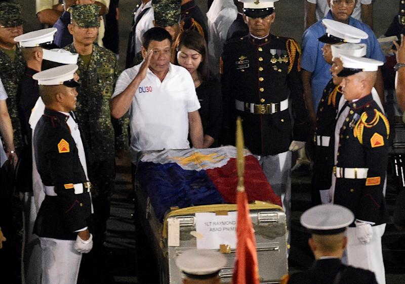 Philippine President Rodrigo Duterte (C) salutes in front of a flag-draped casket of a slain marine in Manila on June 11, 2017 following a firefight with Muslim militants in Marawi