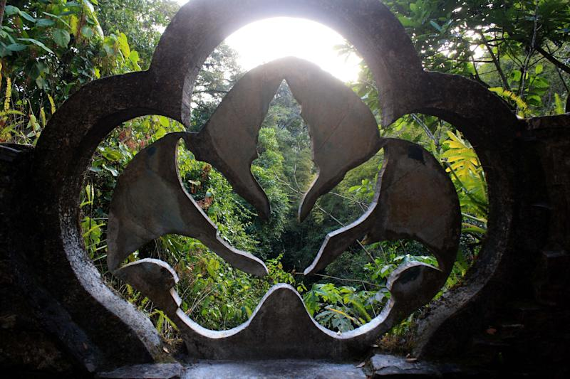 This Jan. 31, 2014 photo shows trees framed through a concrete philodendron sculpture at Las Pozas, a dreamy, little-known garden of surreal art, in Mexico's northeast jungle. Las Pozas is located on a 100-acre (40-hectare) hillside where the Sierra Madre mountains and coastal plains of the northeast state of San Luis Potosi meet. (AP Photo/Teresa de Miguel Escribano)