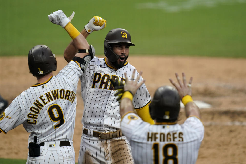 San Diego Padres' Eric Hosmer, facing camera, reacts with teammates after hitting a grand slam during the fifth inning of a baseball game against the Texas Rangers, Thursday, Aug. 20, 2020, in San Diego. (AP Photo/Gregory Bull)