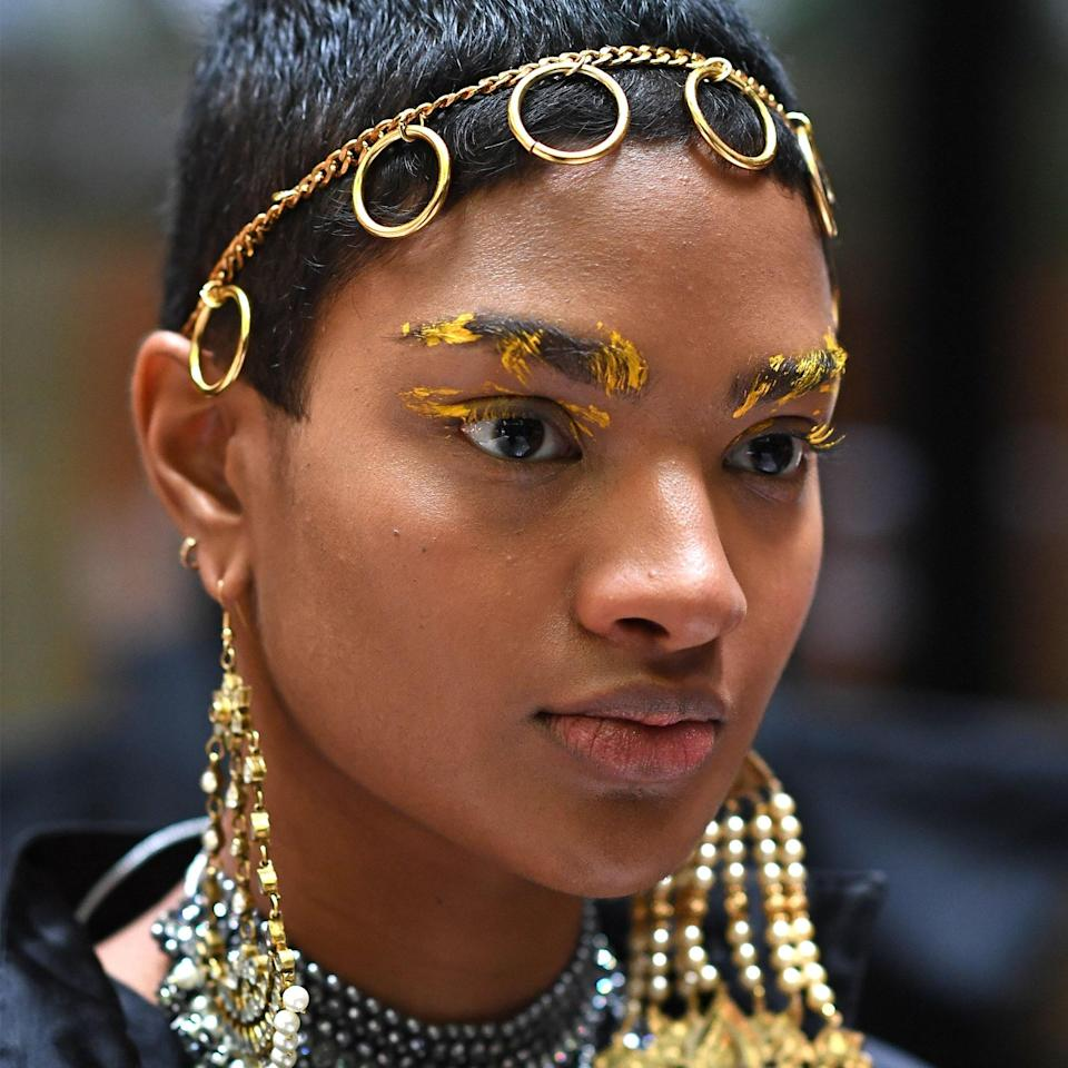 Although the rest of their skin was left bare, abstract strokes of cream liner in yellow, blue, and pink were smudged onto models' brows and lids at Osman's LFW presentation. The color used for this one picked up the golden tones of the ringed headpiece and ornate earrings beautifully.