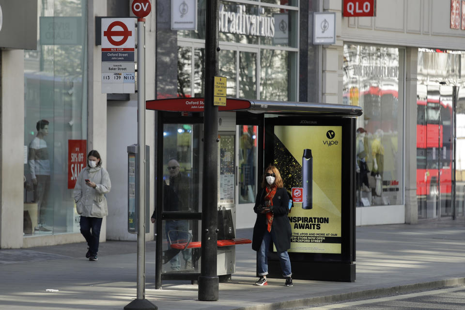 """A masked woman waits at a bus stop on a deserted Oxford Street in London, Tuesday, March 24, 2020. Britain's Prime Minister Boris Johnson on Monday imposed its most draconian peacetime restrictions due to the spread of the coronavirus on businesses and gatherings, health workers begged for more gear, saying they felt like """"cannon fodder."""" For most people, the new coronavirus causes only mild or moderate symptoms. For some it can cause more severe illness. (AP Photo/Matt Dunham)"""