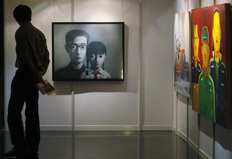 """A man walks past a painting titled """"Bloodline Series"""", center, by Chinese artist Zhang Xiaogang at the Seoul Auction in Hong Kong Tuesday, April 3, 2012. Auctioneers in Hong Kong have sold 10 paintings seized from a South Korean bank that collapsed last year amid a corruption scandal to raise $2.4 million to help repay depositors. The paintings included works by noted Chinese artists Zeng Fanzhi and Zhang Xiaogang and American Julian Schnabel.  (AP Photo/Kin Cheung)"""