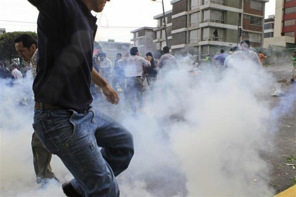 Supporters of Ecuadorean President Rafael Correa run from tear gas as they try to defend Correa in the hospital where he took refuge from the police, in Quito September 30, 2010.