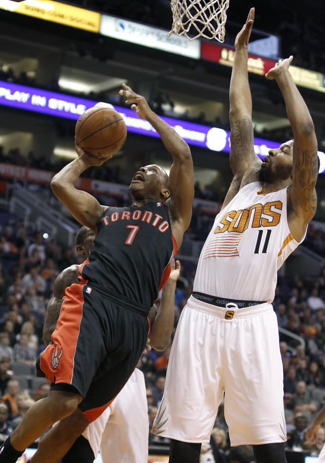 Toronto Raptors' Kyle Lowry (7) drives to the basket for a lay-up as Phoenix Suns' Markieff Morris (11) defends during the second half of an NBA basketball game on Friday, Dec. 6, 2013, in Phoenix. (AP Photo/Ralph Freso)
