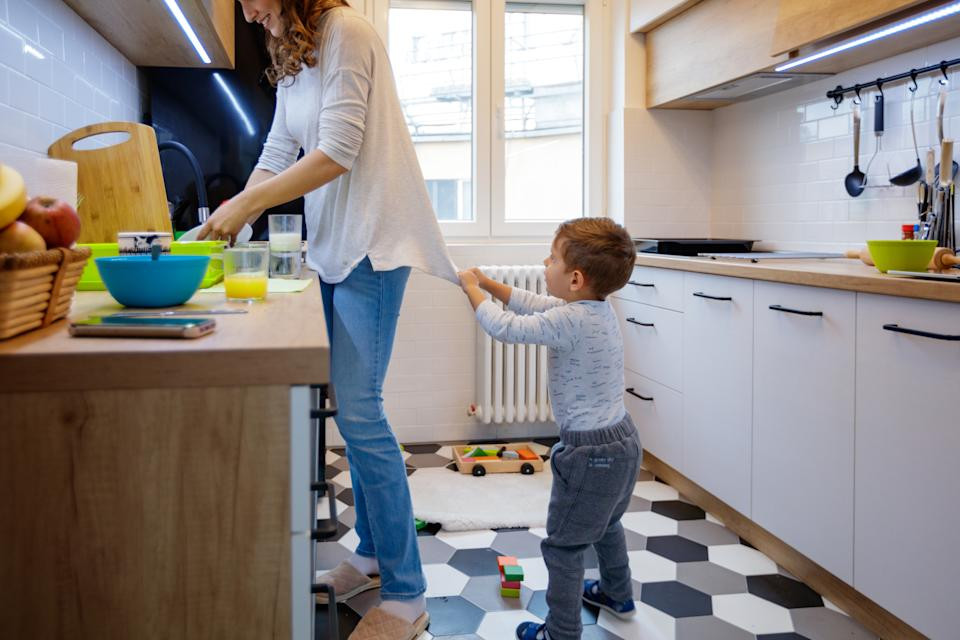 Cute 2.5-year-old boy seeking attention from his mother, pulling her top in the kitchen