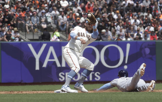 Milwaukee Brewers' Eric Thames, bottom, steals second base under San Francisco Giants shortstop Brandon Crawford during the third inning of a baseball game in San Francisco, Sunday, June 16, 2019. (AP Photo/Jeff Chiu)