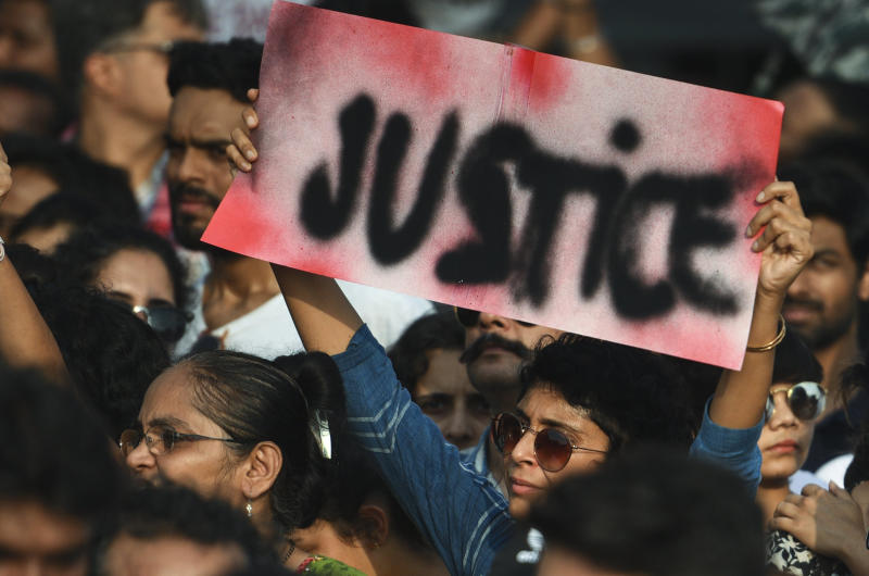 People hold signs as they participate in a protest against the Kathua, Unnao, rape cases and other incidents of rape in India on April 15, 2018 in Mumbai, India.