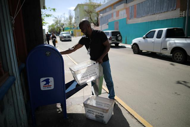 <p>Juan Rivera, from the U.S. Postal Service, picks up the mail at an area affected by Hurricane Maria in the island of Culebra, Puerto Rico, Oct.7, 2017. (Photo: Carlos Barria/Reuters) </p>