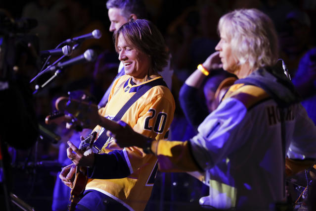 Country music star Keith Urban wears a Nashville Predators jersey as he performs during an intermission of the NHL hockey game between the Predators and the Minnesota Wild on Thursday, Oct. 3, 2019, in Nashville, Tenn. (AP Photo/Mark Humphrey)