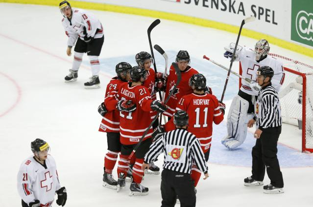 Canada celebrates a goal by Griffin Reinhart in front of Switzerland's goalie Melvin Nyffeler during the first period of their IIHF World Junior Championship ice hockey game in Malmo, Sweden, January 2, 2014. REUTERS/Alexander Demianchuk (SWEDEN - Tags: SPORT ICE HOCKEY)