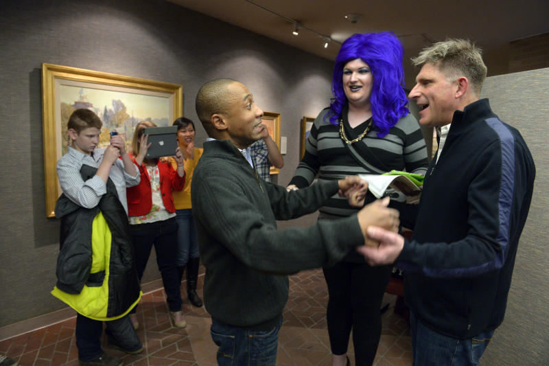 FILE - In this Monday, Dec. 23, 2013, file photo, Greg Jaboin, third from right, expresses his excitement upon being declared married to his partner of 10-years, Steve Kachocki, right, by officiant David Beach at the Salt Lake City County offices in Salt Lake City. The state plans to ask the U.S. Supreme Court to step in and put a halt to gay marriages while they appeal a federal judge's ruling overturning the ban. (AP Photo/The Salt Lake Tribune, Francisco Kjolseth, File)