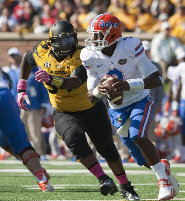 Missouri's Marvin Foster, left, chases Florida quarterback Tyler Murphy, right, out of the pocket during the second quarter of an NCAA college football game Saturday, Oct. 19, 2013, in Columbia, Mo. (AP Photo/L.G. Patterson)