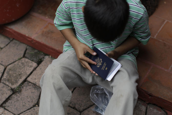 In this Tuesday, July 10, 2012 photo, Rogelio Hernandez Medina, 7, examines his U.S. passport as he waits with his father to get his U.S. birth certificate stamped by Mexican authorities in Malinalco, Mexico. Because of the Byzantine rules of Mexican and U.S. bureaucracies, tens of thousands of U.S. born children of Mexican migrant parents now find themselves without access to basic services in Mexico - unable to officially register in school or sign up for health care at public hospitals and clinics that give free check-ups and medicines. (AP Photo/Dario Lopez-Mills)