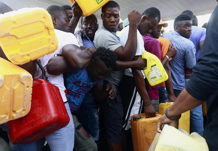 FILE - In this Sept. 4, 2019 file photo, people fight as they line up at a closed gas station, hoping it will open eventually, during a fuel shortage in Port-au-Prince, Haiti. Despite the rarity of his public appearances, Haiti's embattled president has given no indication he will step down amid nearly a month of demonstrations against corruption, spiraling inflation and dwindling supplies of food and gasoline. (AP Photo/Dieu Nalio Chery, File)