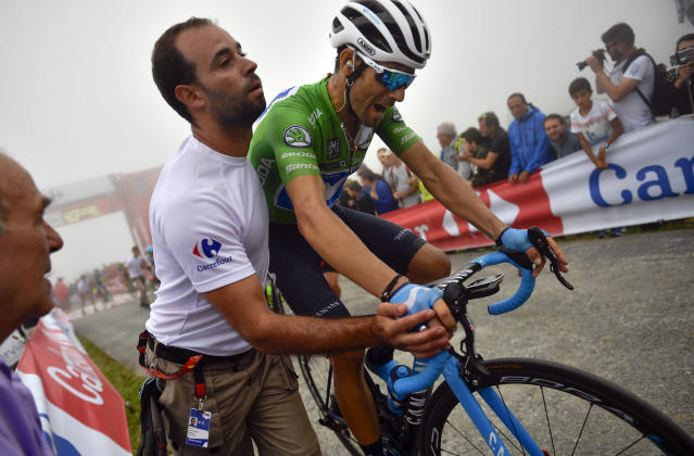 Alejandro Valverde, of Spain, gets help after completing the 17th stage of the Spanish Vuelta cycling race between Getxo and Balcon de Vizcaya, northern Spain, Wednesday, Sept.12, 2018. (AP Photo/Alvaro Barrientos)